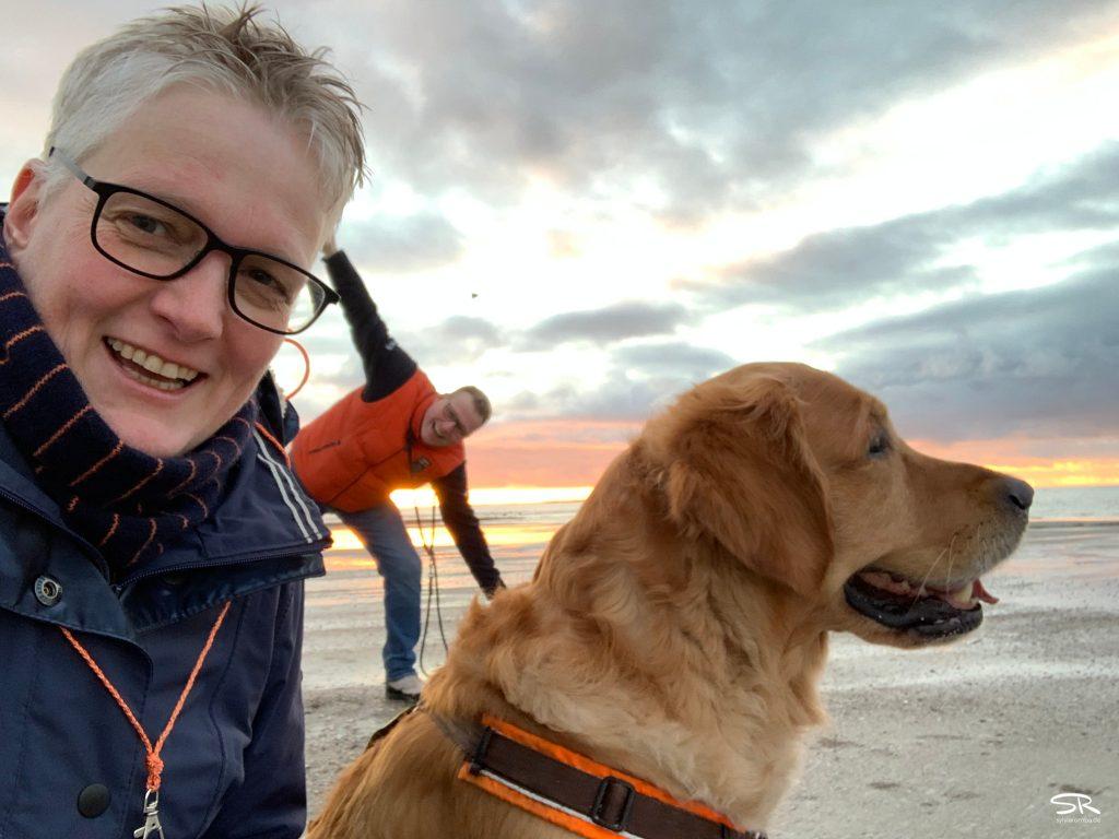 Sylvia & Eric Romba mit Madsen am Strand von Norderney. Sylvia schaut in die Kamera und Madsen sitzt neben ihr mit Blick aufs Meer, während Eric im Hintergrund faxen macht.